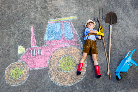 rain boots: Happy little kid boy in straw hat and rain boots having fun with tractor picture drawing with colorful chalks. Children, lifestyle, fun concept. child dreaming of future and profession. Stock Photo
