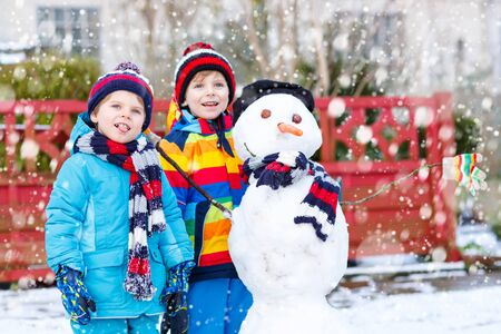 having fun in the snow: Two little siblings kids boys making a snowman, playing and having fun with snow, outdoors  on cold day. Active leisure with children in winter.