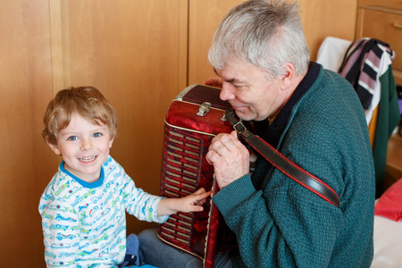 Prodigy: Happy blond little kid boy and his grandfather playing together with accordion. Senior man teaching his grandson, cute toddler to play with music instrument at home.