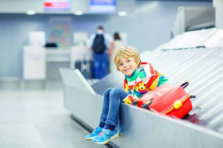 Beautiful little tired kid boy at the airport, traveling. Happy child waiting with kids suitcase on baggage carousel. Canceled flight due to pilot strike. Stock Photo
