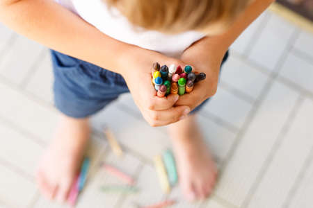 pensil: Closeup of childs hands with lots of colorful wax crayons pencils. Kid preparing stationary and student stuff. Back to school concept Stock Photo