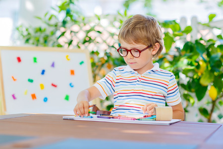 Funny adorable little kid boy with glasses holding wax crayons pens. Happy child and student is back to school and looking at pupils stuff on warm day.