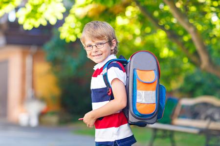 Glückliches kleines Kind Junge mit Brille und Rucksack oder Schulranzen an seinem ersten Tag in der Schule oder Kindergarten. Kind im Freien an warmen sonnigen Tag, zurück zur Schule Konzept
