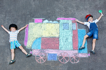 friends having fun: Two little kids boys having fun with train or steam locomotive picture drawing with colorful chalks on ground. Children, lifestyle, fun concept. funny friends playing and dreaming of future and profession.