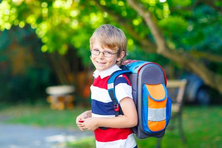 Glückliches kleines Kind Junge mit Brille und Rucksack oder Schulranzen an seinem ersten Tag in der Schule oder Kindergarten. Kind im Freien an warmen sonnigen Tag, zurück zur Schule Konzept Standard-Bild