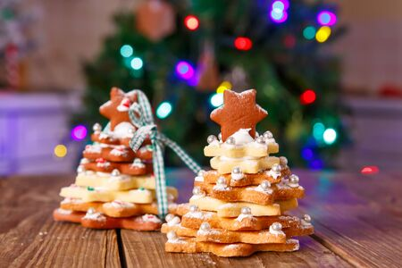 als: Home made baked Christmas gingerbread tree as a gift for family and friends on wooden background. With colorful lights from Christmas tree on background. With icing sugar als snow. Selfmade gift for xmas. Stock Photo