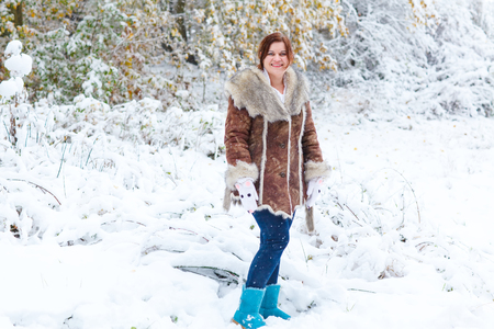 fashon: Young beautiful woman having fun with snow outdoors on beautiful winter day. Girl in fashon winter look walking through park during snowfall Stock Photo