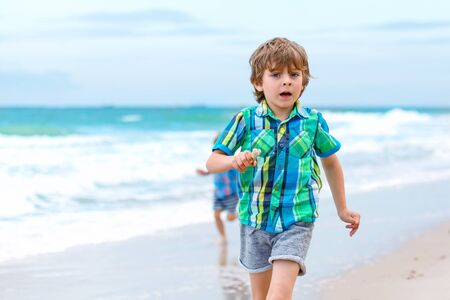 sibling: Two happy little kids boys running on the beach of ocean. Funny cute children, sibling and best friends making vacations and enjoying summer.