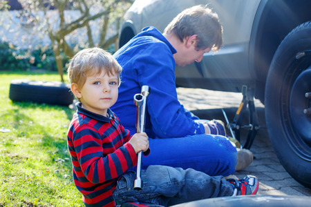 pneumatic tyres: Little blond toddler boy and his father changing wheels on car with pneumatic wrench. Man in uniform teaching his son working with tools.