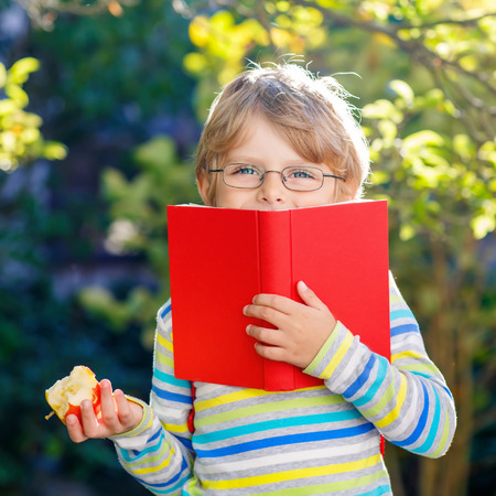 Funny little kid boy with glasses, books, apple and backpack on his first day to school or nursery. Child outdoors on warm sunny day, Back to school concept Stock Photo