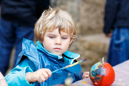 harvest festival: Happy little kid boy on a harvest festival, painting with colors a pumpkin. Child celebrating traditional festival halloween or thanksgiving. Stock Photo