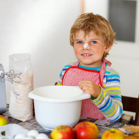 cake mixer: Lovely funny blond little kid boy baking apple cake and muffins in domestic kitchen. Happy child having fun with working with mixer, flour, eggs and fruits at home.