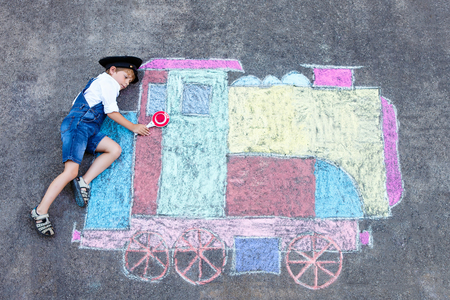 Gelukkig klein kind jongen met plezier met de trein of de stoomlocomotief afbeelding tekenen met kleurrijke krijt op de grond. Kinderen, lifestyle, leuk concept. grappige kind spelen en dromen van de toekomst en beroep. Stockfoto