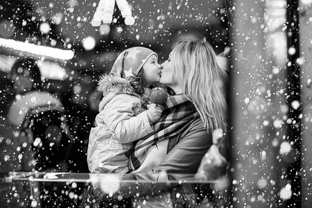 tradition: Beatiful mother and little daughter eating crystalized sugared apple on German Christmas market. Happy family in winter clothes with lights on background. Family, tradition, holiday concept Stock Photo