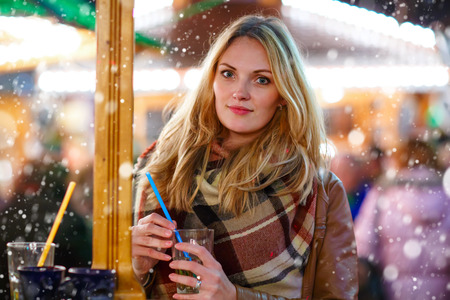 girl punch: Beautiful young woman drinking hot punch, mulled wine on German Christmas market. Happy girl in winter clothes with lights on background. Family, tradition, holiday concept