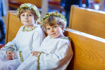 christmas story: Two beautiful little kis in angel clothes for Christmas story in a church. Happy adorable blond children, boys singing and excited about holiday.