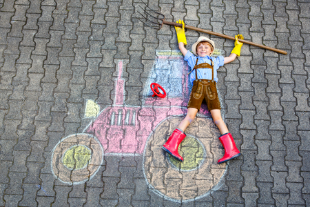 straw hat: Happy little kid boy in straw hat and rain boots having fun with tractor picture drawing with colorful chalks. Children, lifestyle, fun concept. child dreaming of future and profession. Stock Photo