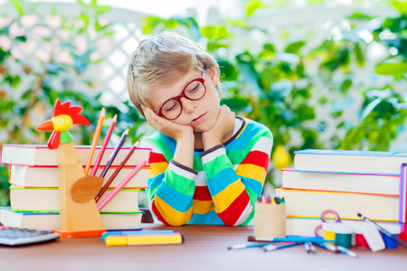 Frustrated sad little kid boy with glasses and lots of pupils stuff like crayons pens, scissors and books. Tired child and student is back to school and happy about begin of lessons. Stock Photo