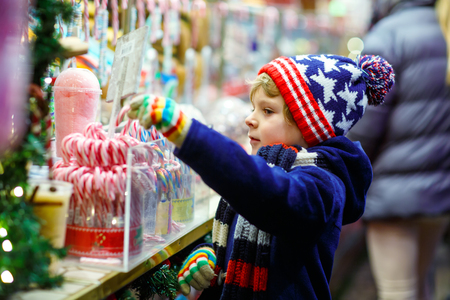weihnachtsmarkt: Little cute kid boy near sweet stand with candy canes. Happy child on Christmas market in Germany. Traditional leisure for families on xmas