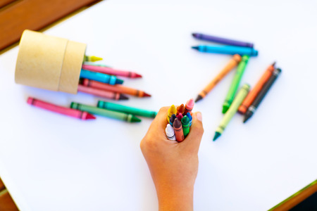 Closeup of childs hands with lots of colorful wax crayons pencils. Kid preparing stationary and student stuff. Back to school concept Stock Photo