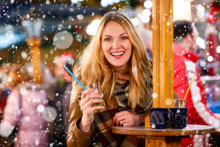 weihnachtsmarkt: Beautiful young woman drinking hot punch, mulled wine on German Christmas market. Happy girl in winter clothes with lights on background. Family, tradition, holiday concept