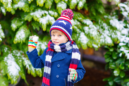 Winter portrait of little kid boy in colorful clothes, outdoors during snowfall. Active outdoors leisure with children in winter on cold snowy days. Happy child having fun with snow Stock Photo