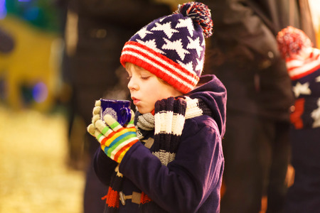 Little cute kid boy with cup of steaming hot chocolate or children punch. Happy child on Christmas market in Germany. Traditional leisure for families on xmas Standard-Bild