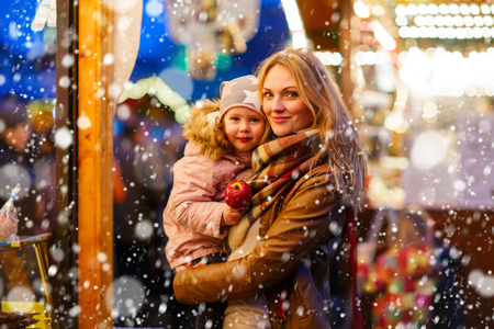 Beatiful mother and little daughter eating crystalized sugared apple on German Christmas market. Happy family in winter clothes with lights on background. Family, tradition, holiday concept Archivio Fotografico