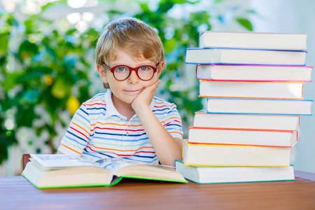 Adorable little kid boy with glasses and stack of colorful books. Cute happy preschool child and student is back to school and reading on warm day.