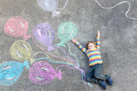 Adorabile ragazzo bambino si diverte con palloncini colorati immagine disegno con gessetti su un terreno. il tempo libero creativo per i bambini all'aperto in estate, per festeggiare il compleanno, carta dell'invito idea