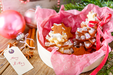 Home made baked Christmas gingerbread tree as a gift for family and friends. Christmas decoration in pink. With icing sugar als snow. Selfmade gift for xmas.