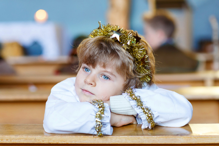 christmas story: Beautiful little kid boy playing an angel in Christmas story in a church. Happy adorable blond child with lights and xmas tree on background. Stock Photo