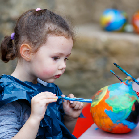 Happy little kid girl on a harvest festival, painting with colors a pumpkin. Child celebrating traditional festival halloween or thanksgiving.