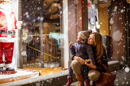 Little toddler girl with mother on Christmas market. Funny happy kid making window shopping with  Santa Claus. holidays, christmas, childhood and people concept. family during winter snowfall