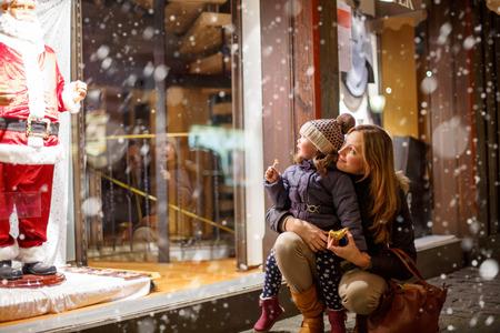 Weinig peutermeisje met moeder op de kerstmarkt. Grappig gelukkig kind het maken van window shopping met de kerstman. vakantie, kerstmis, de kindertijd en mensen concept. familie tijdens de winter sneeuwval