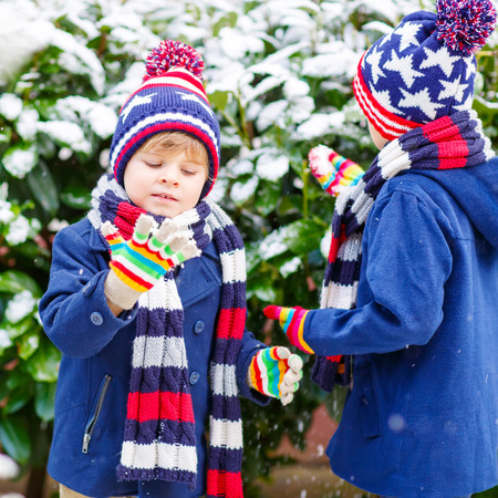 outoors: Two little kid boys in colorful clothes, outdoors during snowfall. Active outoors leisure with children in winter on cold snowy days. Happy siblings having fun with snow Stock Photo
