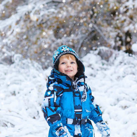 outoors: Winter portrait of kid boy in colorful clothes, outdoors during snowfall. Active outoors leisure with children in winter on cold snowy days. Happy toddler child having fun with snow in forest Stock Photo