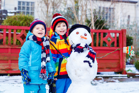 having fun in the snow: Two little siblings boys making a snowman. Kids playing and having fun with snow, outdoors  on cold day. Active outdoors leisure with children in winter.