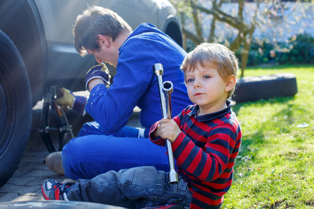 pneumatic tyres: Happy blond kid boy and his father changing wheels on car with pneumatic wrench. Man in uniform teaching his son working with tools.