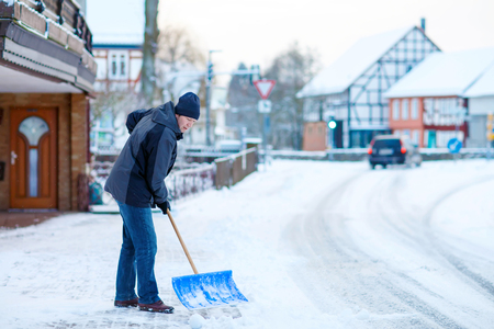 sidewalks: Man with snow shovel cleans sidewalks in winter. Winter time in Europe. Young man in warm winter clothes