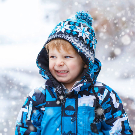 outoors: Winter portrait of funny kid boy in colorful clothes, outdoors during snowfall. Active outoors leisure with children in winter on cold snowy days. Happy toddler child having fun with snow in forest Stock Photo