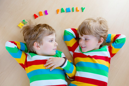 Two little sibling kid boys having fun together, indoors. Children in colorful shirts laughing and smiling. Family concept.