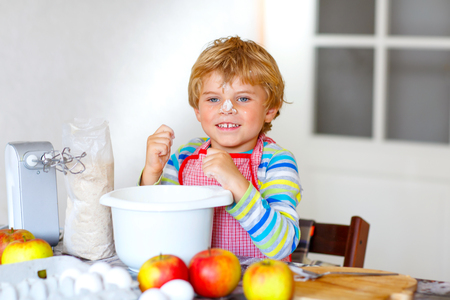 cake mixer: Cute funny blond kid boy baking apple cake in domestic kitchen. Child having fun with working with mixer, flour, eggs and fruits. With flour on nose Stock Photo