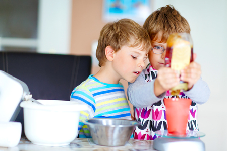 cake mixer: Two little funny brothers baking apple cake in domestic kitchen. Kid boys having fun with working with mixer, eggs and honey