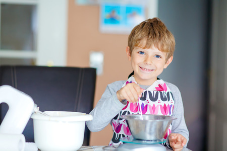 cake mixer: Cute funny blond kid boy baking apple cake in domestic kitchen. Child having fun with helping and working with mixer, flour, eggs and fruits. Stock Photo
