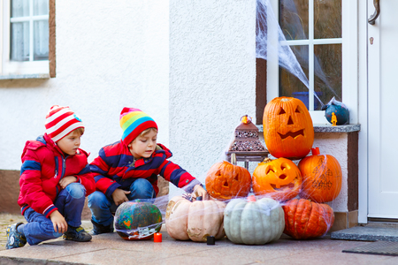 Two little kid boys sitting with traditional jack-o-lanterns pumpkins for halloween by the decorated scary door, outdoors. Children having fun and celebrating holiday.