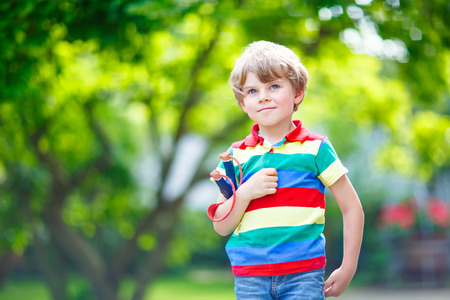 rowdy: Funny little kid boy shooting wooden slingshot against green tree background. Child having fun in summer.