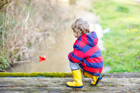 Happy little kid boy in yellow rain boots playing with paper ship by a creek on spring or autumn day. Active leisure for children. Child having fun outdoors and wearing colorful clothes.