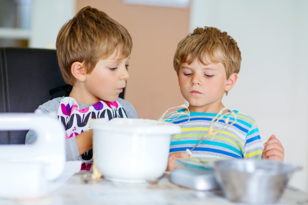 cake mixer: Two little funny twins brothers baking apple cake in domestic kitchen. Kid boys having fun with working with mixer, eggs and honey. Children tasting dough