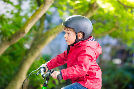 fall protection: Active little preschool kid boy in helmet biking on bicycle in the autumn park. Happy child in colorful clothes with yellow fall foliage on background. Safety and protection for children. Stock Photo